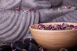 Buddha mit Bambus, Massage Steinen und Schale voll Blüten