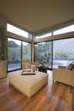 Neutrally upholstered furniture in room corner with floor to ceiling windows