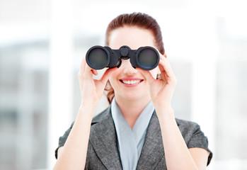 Attractive businesswoman using binoculars