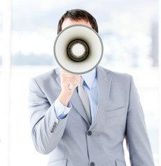 Portrait of an young businessman using a megaphone