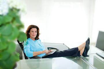 Geschäftsfrau gelassen am Schreibtisch