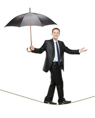 A person holding an umbrella and walking on a high tightrope