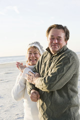Senior couple in sweaters together on beach