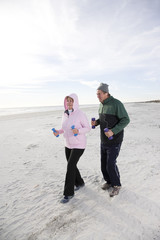 Senior couple exercising, walking on beach