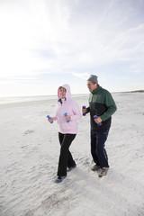 Senior couple exercising, walking on beach