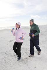 Senior couple exercising, running on beach