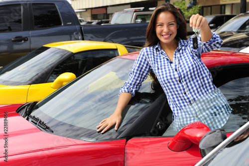 woman showing key of new sports car