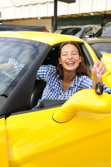 woman showing sitting inside of her new sports car