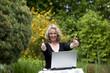 hübsche lächelnde blonde Frau mit Laptop zeigt Daumen hoch