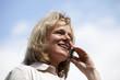 lächelnde hübsche blonde Frau telefoniert mit Mobiltelefon