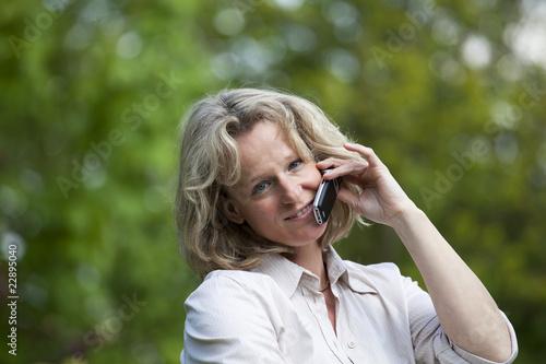 verliebte hübsch blonde Frau mit Mobiltelefon