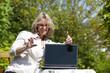 lächelnde hübsche blonde Frau mit Laptop und Visitenkarte