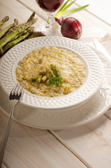 asparagus rice with fork on dish and red wine