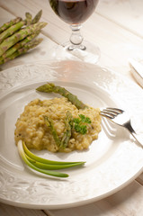 asparagus rice with fork over dish and red wine