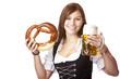Frau im Dirndl hält Oktoberfest Bierkrug und Breze - Prost