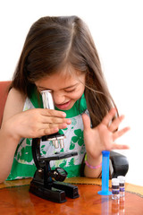 Girl looks through microscope