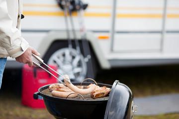 mann steht auf dem campingplatz am grill
