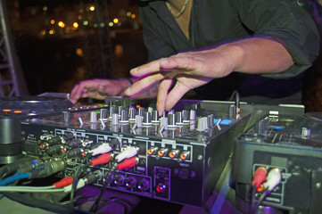 DJ mixing music on a mixer desk