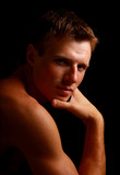 Shadowy dark close-up portrait of young good looking male model poster