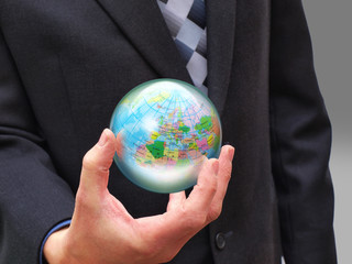 Businessman with glass sphere containing the world