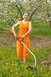 woman doing work in her garden with grass-mower