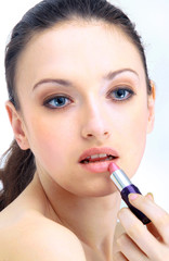 Portrait of beautiful woman applying lipstick using lip