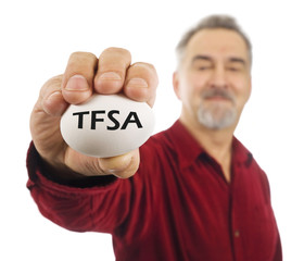 Mature man holds a white nest egg with TFSA on it.