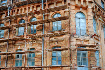 scaffolds round an old brick building