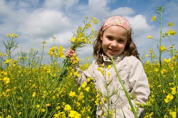 Mädchen mit Blumenstraus im Rapsfeld