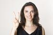 Hübsche Frau zeigt mit zwei Fingern die Zahl 2 an