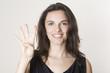 Hübsche Frau zeigt mit vier Fingern die Zahl 4 an