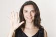 Hübsche Frau zeigt mit fünf Fingern die Zahl fünf an