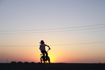 Girl rides bicycle in sunset
