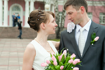 Young loving wedding couple with bunch of flowers