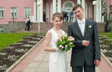 Young loving wedding couple near registry office