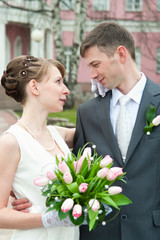 Young loving newlywed pair with bunch of flowers.