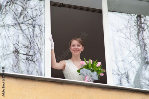 Young bride in home window opening with flowers