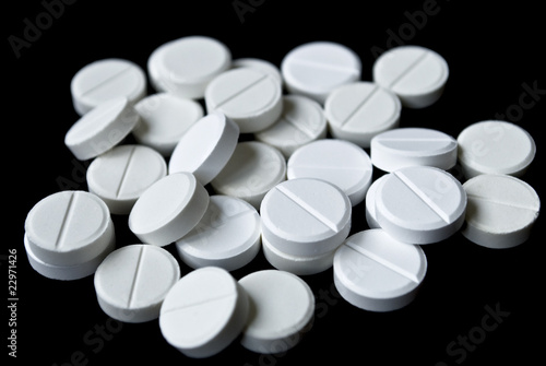 Scattering of white tablets on black background