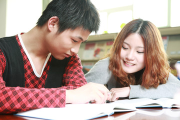 asian boy and girl studying in library