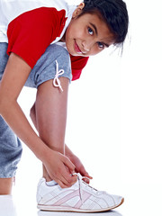 young girl tying her sports shoes isolated on white background