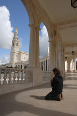 Men praying with Fatima (Portugal) temple as background