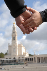 Hands Fatima (Portugal) temple as background