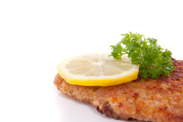a breaded wiener schnitzel with lemon and parsley isolate dover