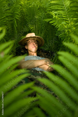 Hiker resting in the shade of the undergrowth of fern.