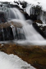 soft waterfall on the rocks with ice