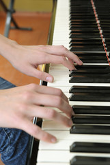Hands above keys of the piano