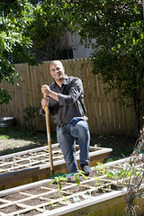 Man working on vegetable garden in backyard