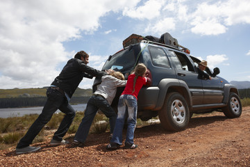 Father and kids pushing a car