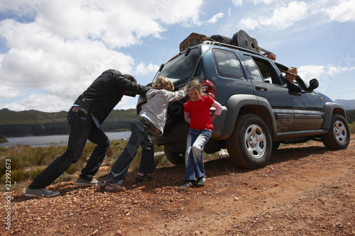 Family pushing broken car
