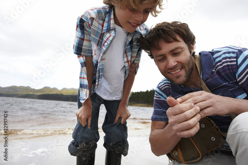 Father and son looking at ladybug